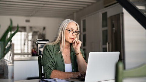 En kvinne sitter foran laptopen.
