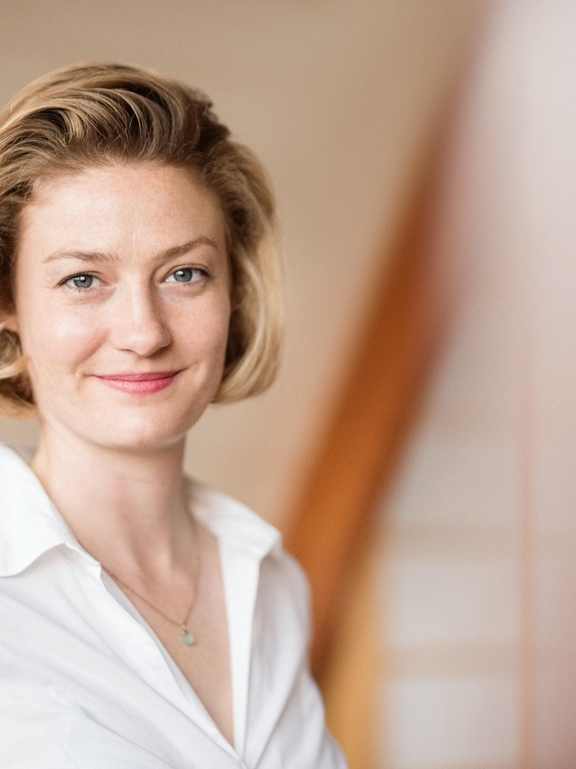 Kvinne i hvit skjorte smiler i kamera