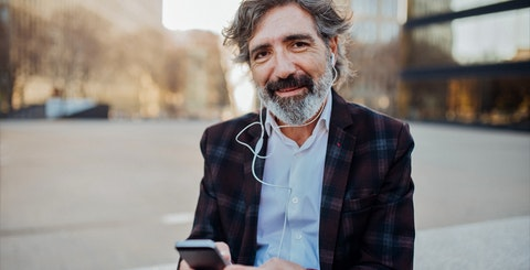 Skjeggete mann med mobil og hodetelefoner smiler inn i kameraet