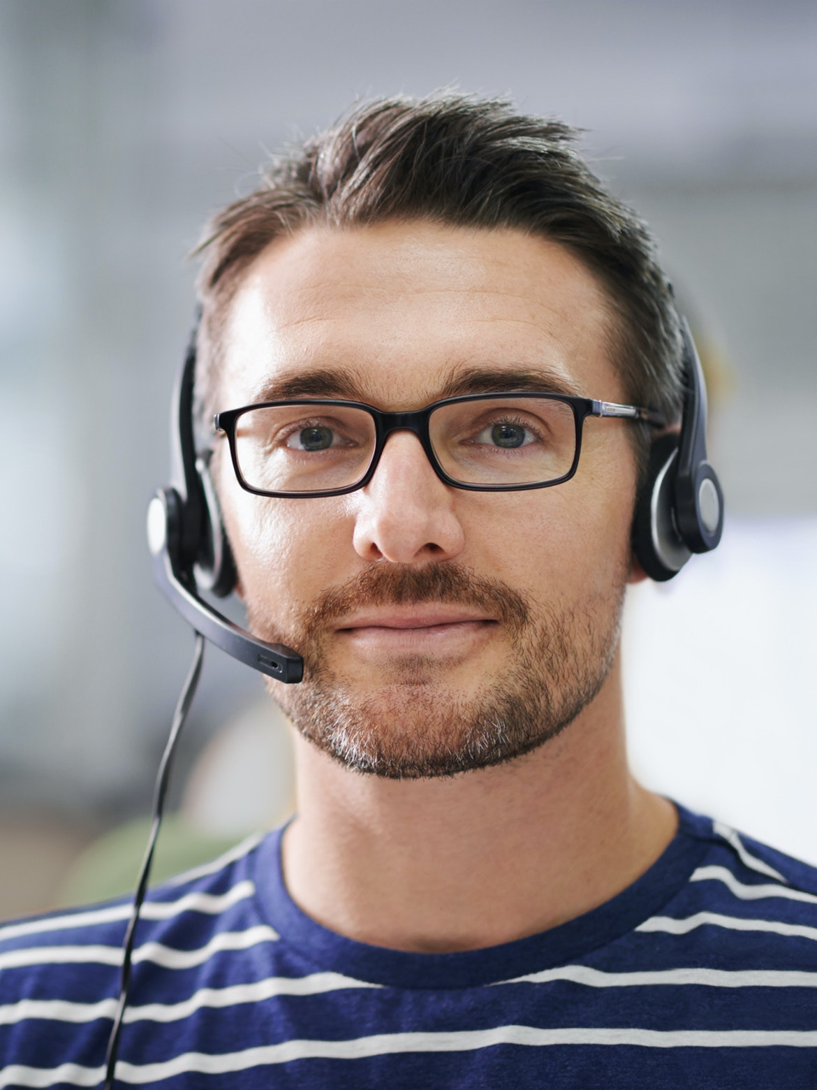 Mann i kundeservice med hodetelefoner ser i kamera