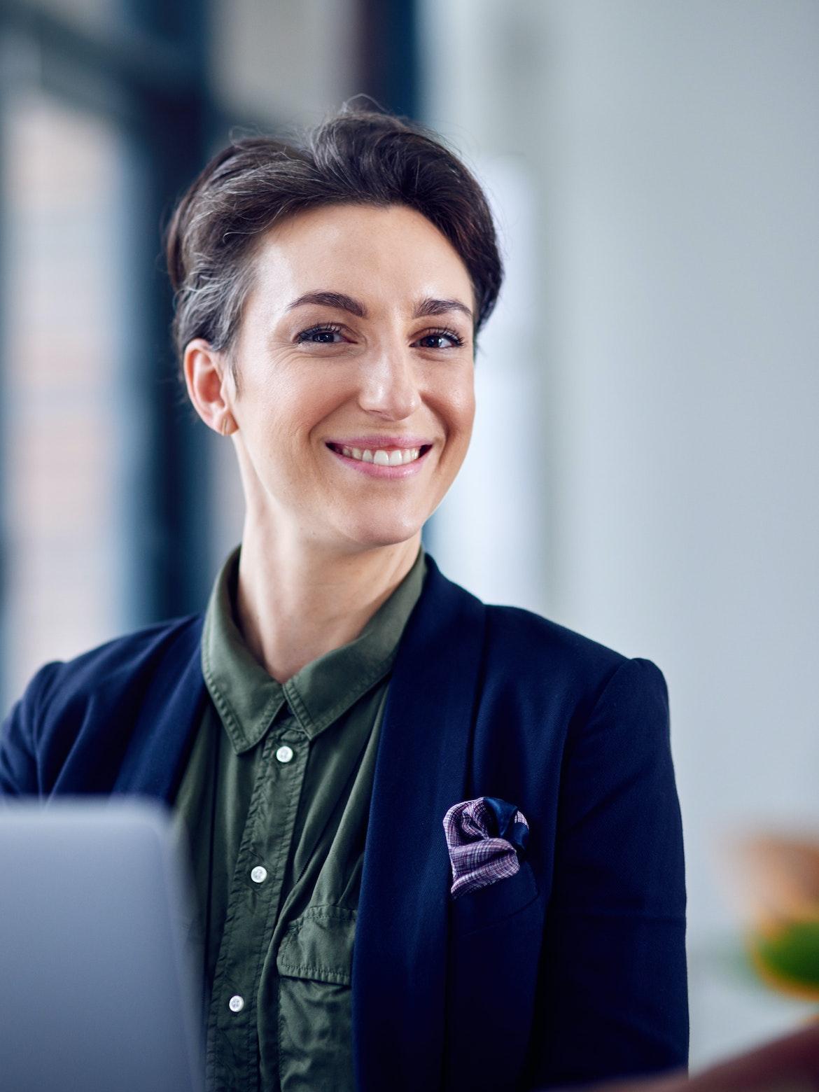 Kvinne som sitter ved pulten og smiler i kameraet.