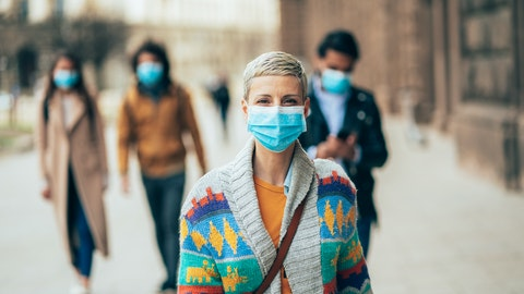 Fire mennesker med munnbind går bortover veien.
