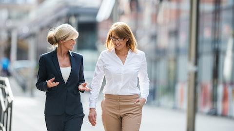To forretningskvinner som prater sammen mens de går i byen.
