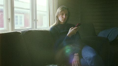 Kvinne som sitter i sofaen og bruker mobilen.