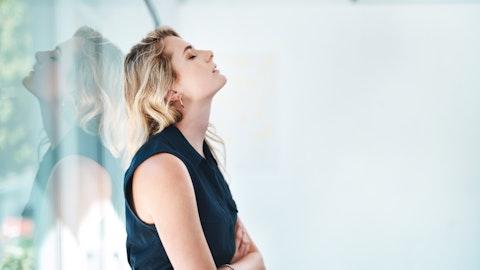Ung blond kvinne som slapper av mot en glassvegg.