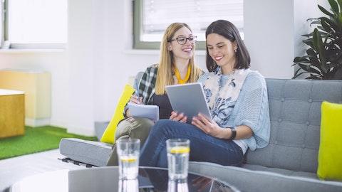 To jenter som sitter å sofaen med en iPad.