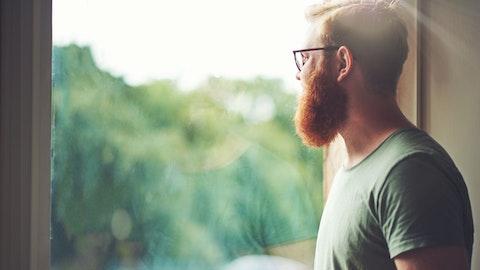 En mann med kaffekopp ser ut av vinduet.