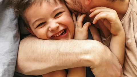 Far som klemmer barnet sitt.