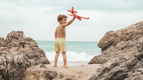 Et barn som leker med et lekefly på stranden.