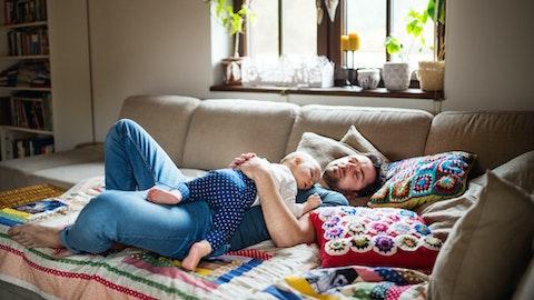 En mann ligger på sofaen. Barnet hans sover på magen hans.