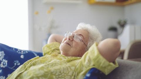Eldre fornøyd dame som slapper av på sofaen.