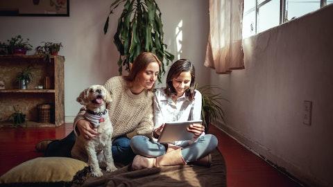 To personer som ser på en ipad med en hund.