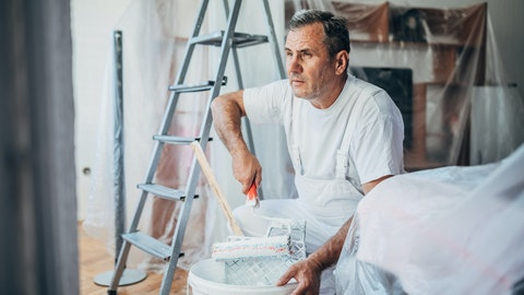 Eldre mann som maler et rom.