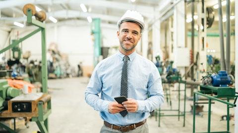 En glad mann i dress på byggeplass.