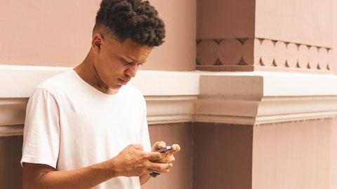 Ung mann som ser ned på mobilen.