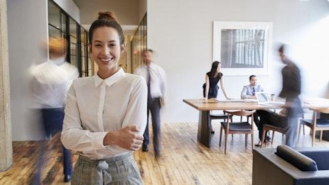 Ung kvinne smiler på et kontor med andre ansatte
