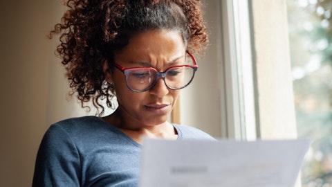 Konsentrert kvinne med briller leser et dokument