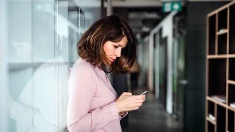 En kvinne stirrer på mobilen og ser bekymret ut.