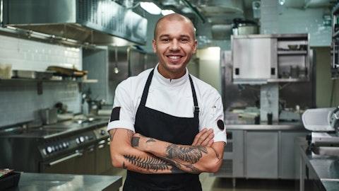 Smilende kokk med tatoveringer krysser armene på kjøkkenet