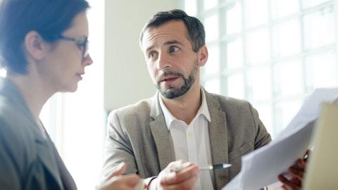 En forretningsmann er i en samtale og holder et dokument.