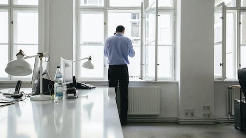 Forretningsmann snakker på mobilen og står ved vinduet på et tomt kontor