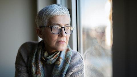 Tankefull kvinne med kort grått hår stirrer ut av vinduet.