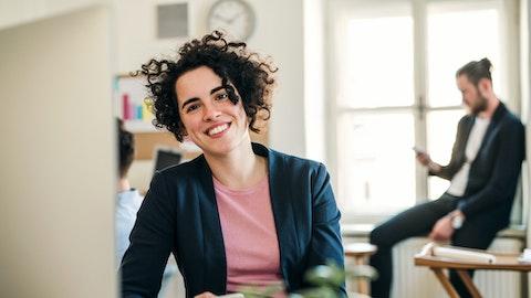En kvinne med mørke krøller smiler bredt på kontoret