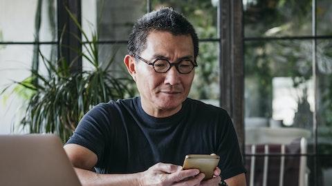En mann med briller ser på mobilen sin.