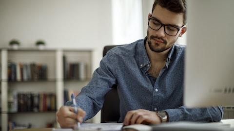 En mann sitter ved et skrivebord og skriver.