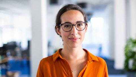 En kvinne med briller smiler mot kameraet.
