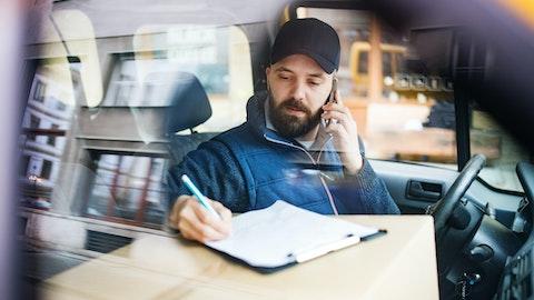 En ung mann med skjegg sitter i bilen og skriver under på et papir.