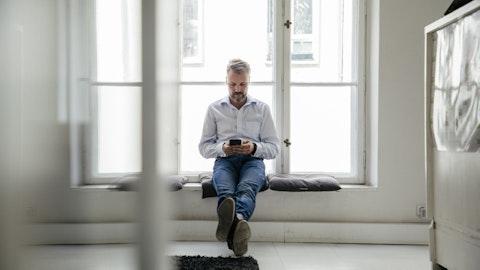 En mann sitter med mobiltelefonen.