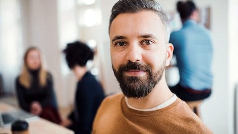 Mann på kontoret ser i kamera med selv-tillit