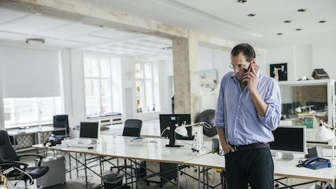 Forretningsmann på et tomt kontor snakker med noen på mobil