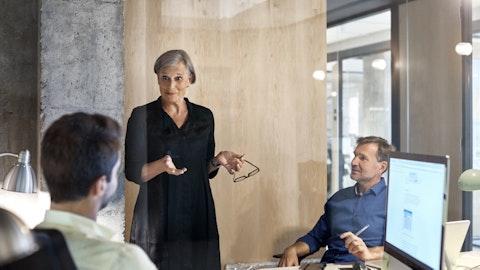 Forretningskvinne snakker med to partnere i et møte