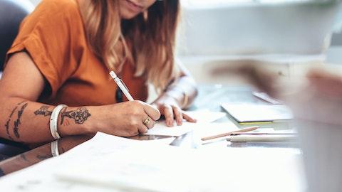 En kvinne med tatoveringer sitter og skriver på et ark.