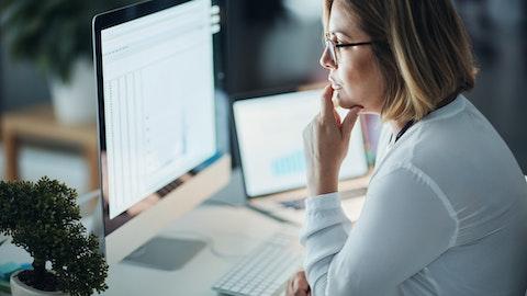 Forretningskvinne ser konsentrert på PC-skjerm.