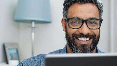 Mann som smiler og ser over skjermen sin i kameraet