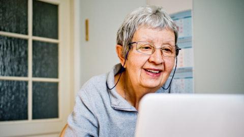 En eldre kvinne sitter foran datamaskinen.