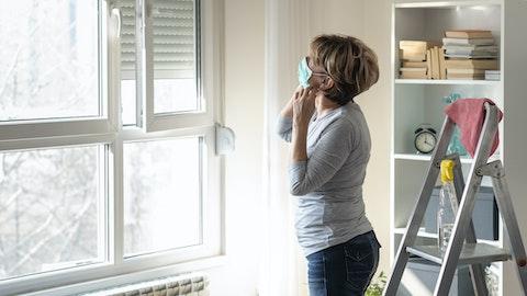 Kvinne med støvmaske står å ser på veggen.