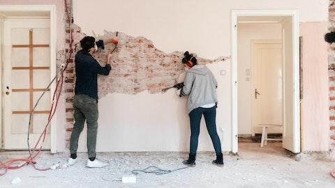 To personer river ned en vegg.