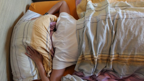 En person ligger i sengen med puten over hodet.