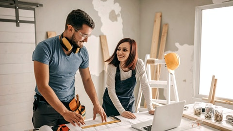 Mann og dame arbeider over en datamaskin.