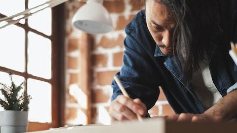 En mann lener seg over bordet og tegner.