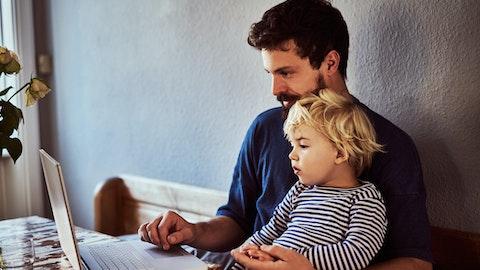 Far og barn ser på datamaskin