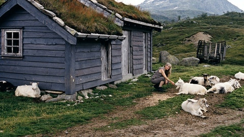 En dame sitter foran en hytte på fjellet og klapper på en geit.
