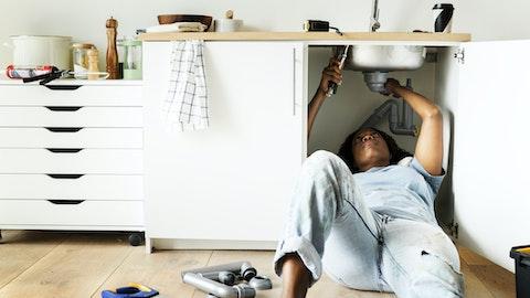 Kvinne ligger under vasken og skrur.