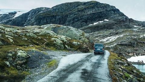 En bil kjører på en vei i fjellet.