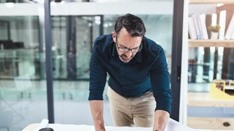 En mann lener seg på et bord med papirer.