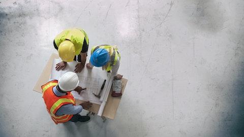 Tre entreprenører som står bøyd over et bord og samarbeider med et prosjekt.